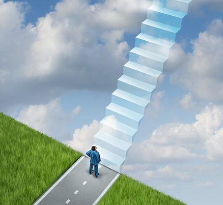 Success plan business concept with a businessman at the end of the road on the edge of a cliff using his vision and leadership skills to imagine the future successful path of opportunity as a staircase of going up to heaven.